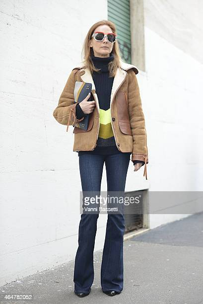 A guest poses wearing a Coach jacket and Jerome Dreyfuss clutch on February 28 2015 in Milan Italy