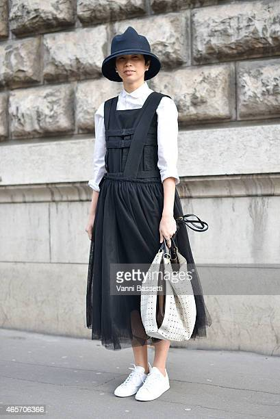 A guest poses wearing a Cos shirt Comme des Garcons dress and Tod's bag on Day 7 of Paris Fashion Week Womenswear FW15 on March 9 2015 in Paris France