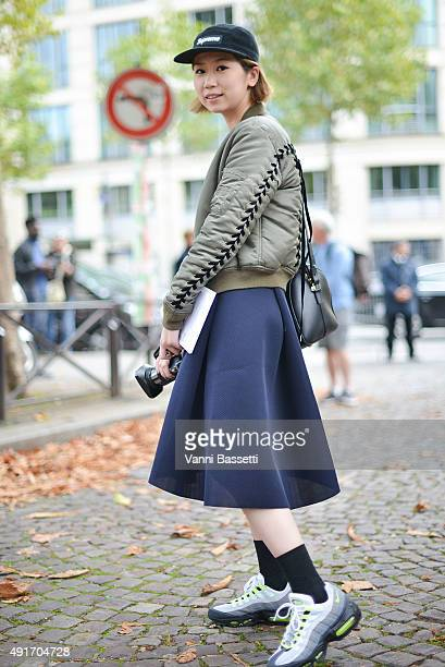 A guest poses wearing a GVGV bomber jacket Nike shoes and Supreme cap before the Miu Miu show at the Palais de Iena during Paris Fashion Week SS16 on...