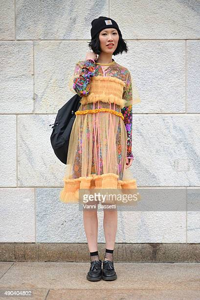 A guest poses wearing a Molly Goddard dress and a Carhart beanie before the Arthur Arbesser show during the Milan Fashion Week Spring/Summer 16 on...