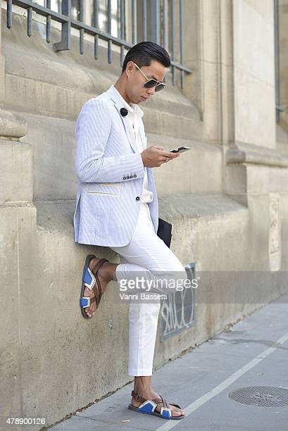 A guest poses wearing a Thom Browne suit before the Saint Laurent show at the Carreau du Temple on June 28 2015 in Paris France