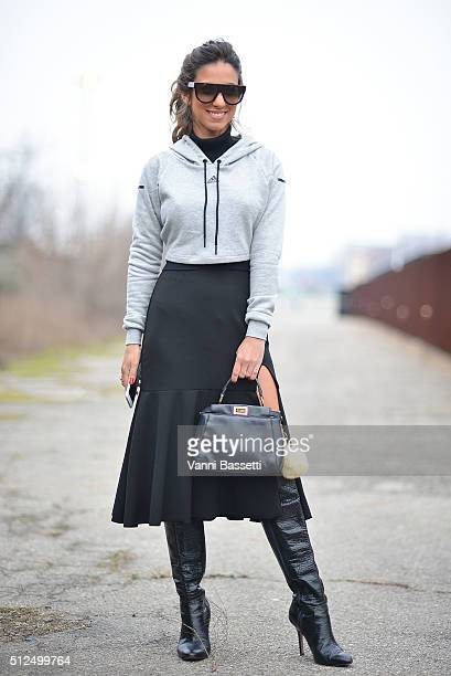 A guest poses wearing an Adidas sweatshirt and a Fendi bag before the Diesel Black Gold show during the Milan Fashion Week Fall/Winter 2016/17 on...