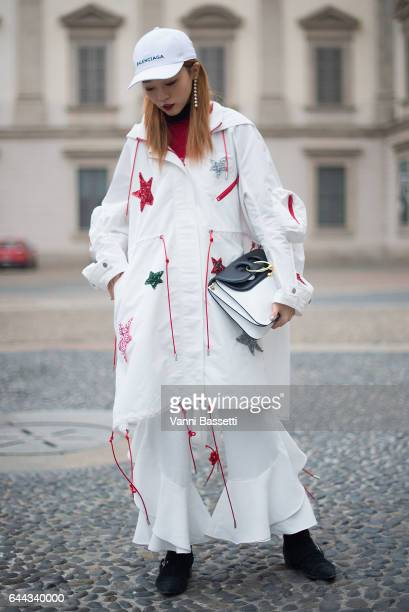 A guest poses wearing an Angel Chen coat JW Anderson bag and Balenciaga cap after the Angel Chen show during Milan Fashion Week Fall/Winter 2017/18...
