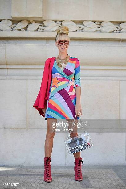 A guest poses wearing an Asos jacket Diane Von Furstenberg dress Miu Miu shoes and Chanel bag on September 27 2014 in Paris France