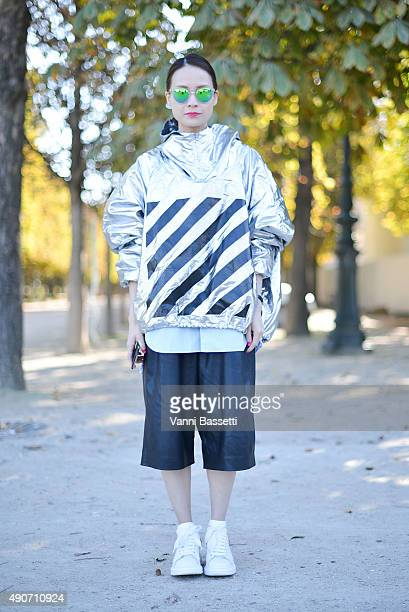 A guest poses wearing an Off White jacket after the Margiela show at the Jardin des Tuileries during Paris Fashion Week SS16 on September 30 2015 in...