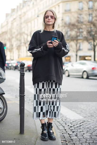 A guest poses wearing an OffWhite sweater and Balenciaga shoes after the Balmain show at the Hotel Potocki during Paris Fashion Week Womenswear FW...