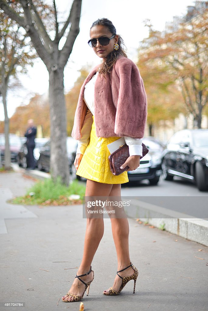 A guest poses wearing Miu Miu skirt and coat before the Miu Miu show at the Palais de Iena during Paris Fashion Week SS16 on October 7 2015 in Paris...
