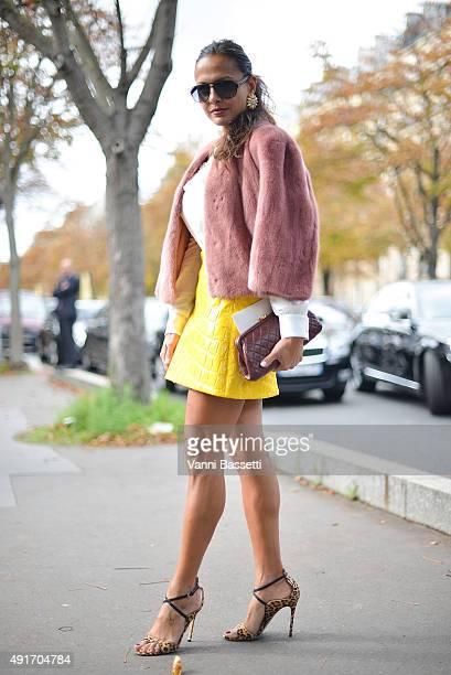 A guest poses wearing Miu Miu skirt and coat before the Miu Miu show at the Palais de Iena during Paris Fashion Week SS16 on October 7 2015 in Paris...