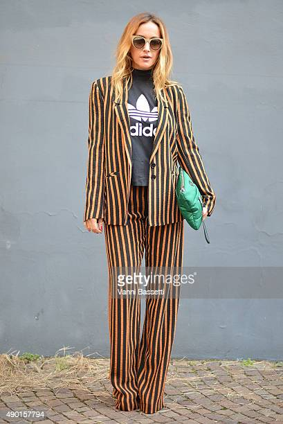 A guest poses wearing Patrizia Pepe jacket and pants Adidas tshirt and Prada clutch before the Antonio Marras show during the Milan Fashion Week...