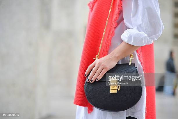 A guest poses with a Chloe bag before the John Galliano show at the Palais de Tokyo during Paris Fashion Week SS16 on October 4 2015 in Paris France