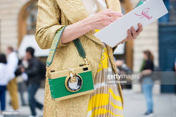 A guest poses with a Dolce and Gabbana camera bag after the Schiaparelli show at Place Vendome during Paris Fashion Week Haute Couture FW 17/18 on...
