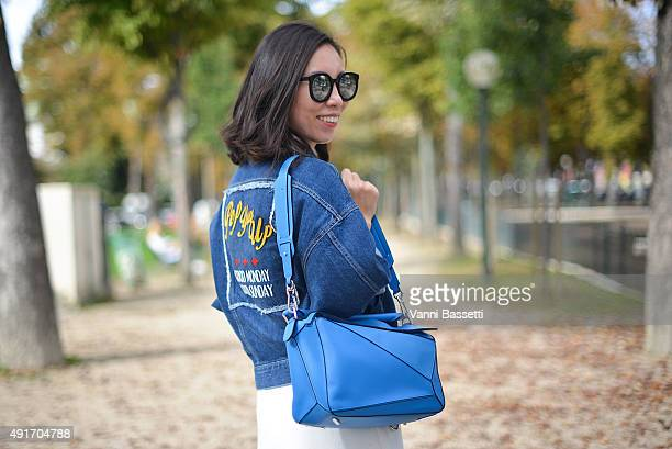 A guest poses with a Loewe bag after the Moncler Gamme Rouge show at the Grand Palais during Paris Fashion Week SS16 on October 7 2015 in Paris France