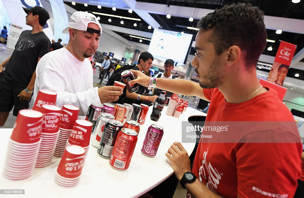 A guest (L) receives a Coca-Cola beverage at FAN FEST during the 2016 BET Experience on June 25, 2016 in Los Angeles, California.