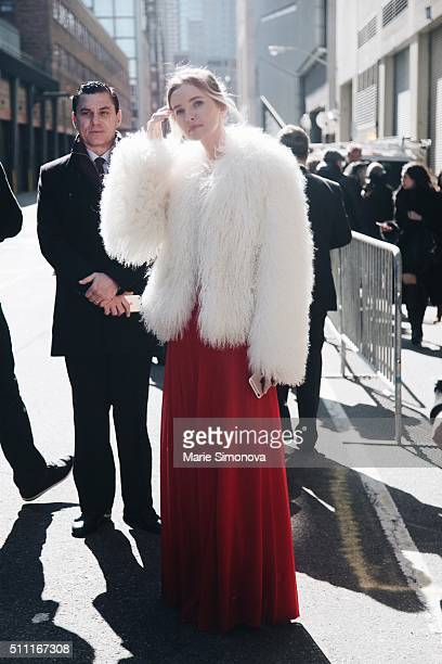 A guest seen after Ralph Lauren runway show during New York Fashion Week wearing white furs and red long dress at Women's Fall/Winter 2016 on...