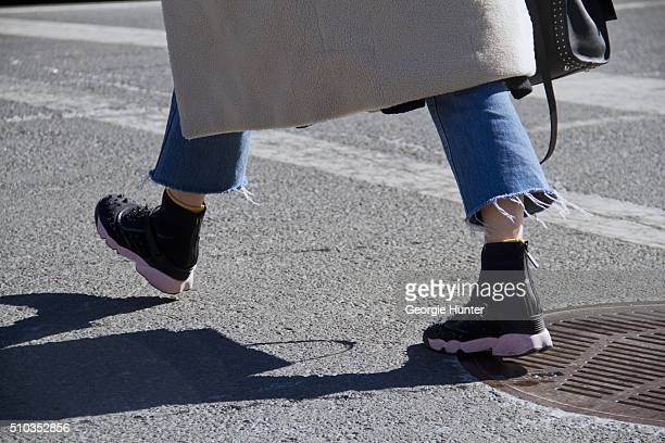Guest seen at Skylight Clarkson Sq outside the Derek Lam show wearing ripped jeans and black and pink sneakers during New York Fashion Week Women's...