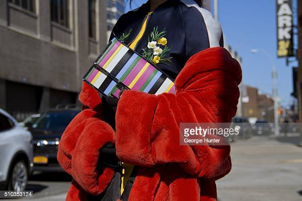 Guest seen at Skylight Clarkson Sq outside the Derek Lam show wearing silk bomber jacket red fur coat and multicolored striped clutch bag during New...