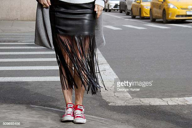 Guest seen at Skylight Clarkson Sq outside the Erin Fetherston show wearing black leather fringed skirt with red Converse sneakers during New York...