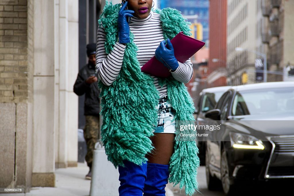 Guest seen at Skylight Clarkson Sq. outside the Erin Fetherston show wearing wool green sleeveless coat, thigh high blue boots, blue leather gloves, striped top and purple leather clutch bag during New York Fashion Week: Women's Fall/Winter 2016 on February 11, 2016 in New York City.