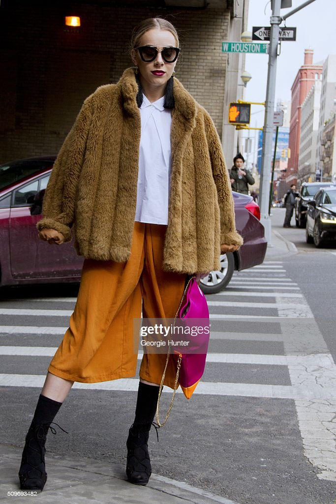 Guest seen at Skylight Clarkson Sq. outside the Erin Fetherston show wearing orange cropped pants, black boots, pink and orange bag, tan fur coat, white shirt, black tassle earrings and sunglasses during New York Fashion Week: Women's Fall/Winter 2016 on February 11, 2016 in New York City.