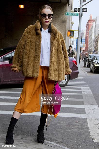 Guest seen at Skylight Clarkson Sq outside the Erin Fetherston show wearing orange cropped pants black boots pink and orange bag tan fur coat white...