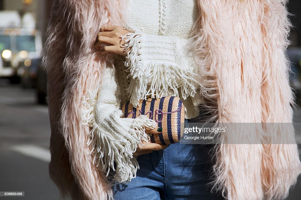 Guest seen at Skylight Clarkson Sq. outside the Erin Fetherston show wearing pink faux fur coat, jeans, cream sweater and striped clutch bag during New York Fashion Week: Women's Fall/Winter 2016 on February 11, 2016 in New York City.