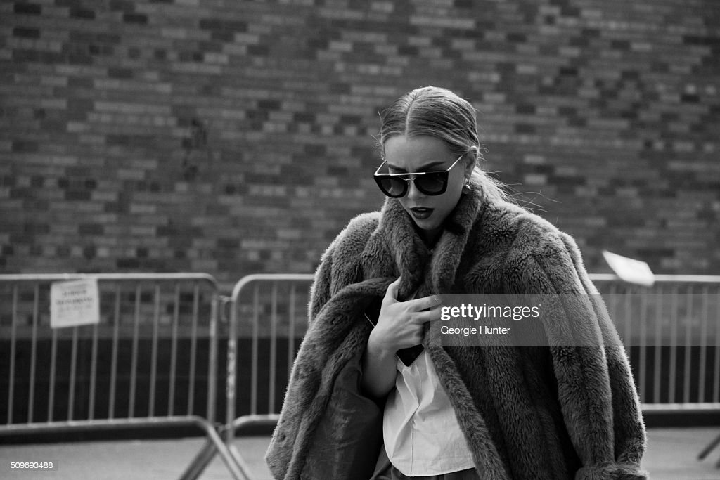 Guest seen at Skylight Clarkson Sq. outside the Erin Fetherston show wearing tan fur coat, white shirt, black tassle earrings and sunglasses during New York Fashion Week: Women's Fall/Winter 2016 on February 11, 2016 in New York City.