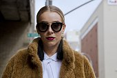 Guest seen at Skylight Clarkson Sq outside the Erin Fetherston show wearing tan fur coat white shirt black tassle earrings and sunglasses during New...