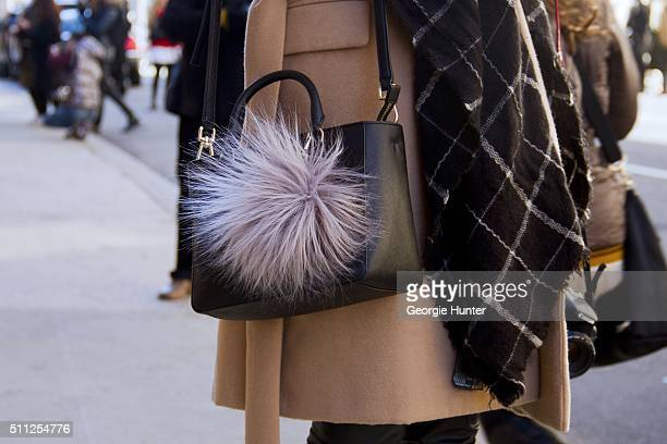 Guest seen at Skylight Clarkson Sq outside the Ralph Lauren show with black leather bag with lilac pom pom during New York Fashion Week Women's...
