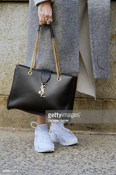 Guest seen at The Arc Skylight at Moynihan Station outside the Concept Korea show wearing white Nike sneakers grey coat and Yves Saint Laurent black...