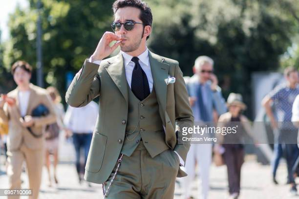 A guest smokeing and wearing an olive suit and vest navy tie sunglasses is seen during Pitti Immagine Uomo 92 at Fortezza Da Basso on June 13 2017 in...