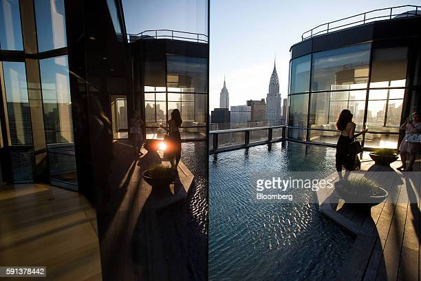 A guest stands for a photograph during a pool party in the penthouse apartment at the 50 United Nations Plaza building in New York US on Tuesday June...