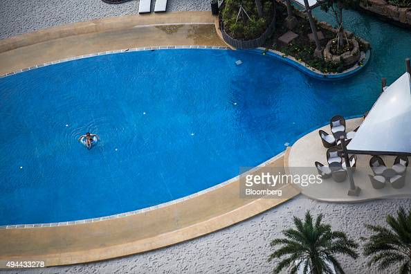 A guest swims in the swimming pool at Studio City casino resort developed by Melco Crown Entertainment Ltd in Macau China on Tuesday Oct 27 2015...