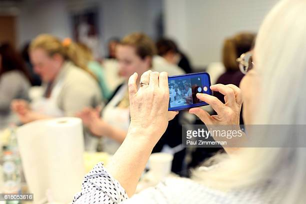 A guest takes a photo at Cake Decorating Master Class hosted by Sylvia Weinstock at Institute of Culinary Education on October 16 2016 in New York...