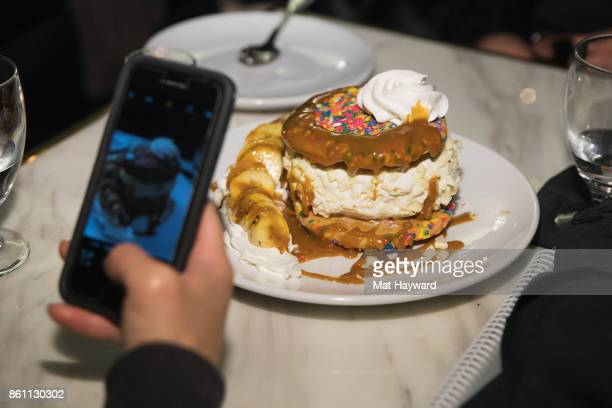A guest takes a photo of an ice cream sandwich at Sugar Factory American Brassiere on October 13 2017 in Bellevue Washington