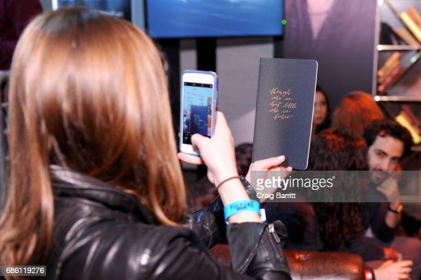 A guest takes a photo of their personalized Calligraphy Notebook in the Vulture Lounge during the 2017 Vulture Festival at Highline Stages on May 20...