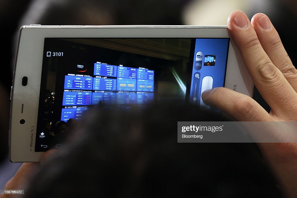 A guest takes photographs of an electronic board displaying the closing figure of the Nikkei 225 Stock Average on the last trading day of the year at the Tokyo Stock Exchange (TSE) in Tokyo, Japan, on Friday, Dec. 28, 2012. Japanese stocks rose, with the Nikkei 225 Stock Average capping its biggest yearly advance since 2005, as the yen weakened after consumer prices and industrial production data fueled speculation the central bank will respond to calls for more stimulus. Photographer: Kiyoshi Ota/Bloomberg via Getty Images