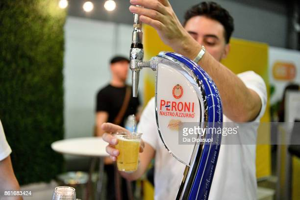 A guest tastes Peroni at the Food Network Cooking Channel New York City Wine Food Festival Presented By CocaCola Grand Tasting presented by ShopRite...