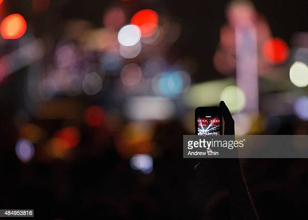 A guest uses a mobile phone to record Jon Bon Jovi of Bon Jovi's performance at Rogers Arena on August 22 2015 in Vancouver Canada