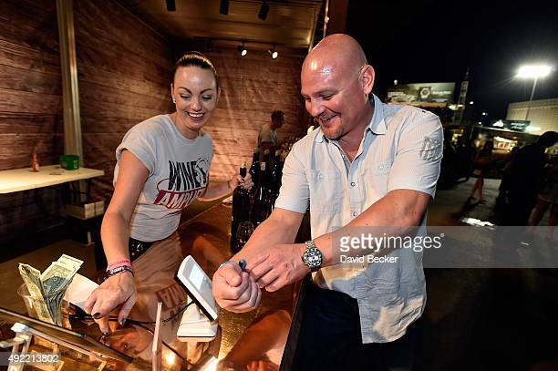A guest uses a RFID embedded wristband to make a purchase at the 10th annual Wine Amplified festival at the Las Vegas Village on October 10 2015 in...