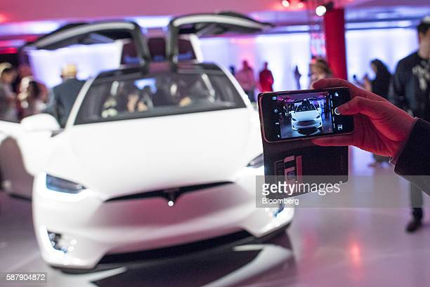 A guest uses a smartphone to take a photograph of a Tesla Motors Inc Model X electric vehicle on display at the company's new showroom in San...
