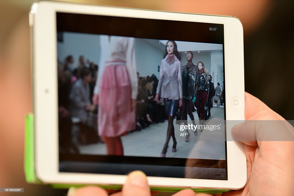 A guest uses an iPad to record the Vivienne Westwood Red Label show at the 2013 Autumn/Winter London Fashion Week in London on February 17, 2013.