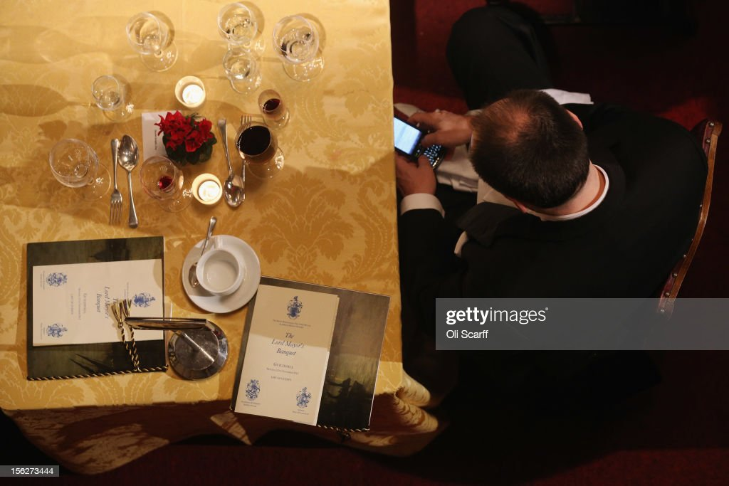 A guest uses his mobile phone as he attends The Lord Mayor's Banquet in the Guildhall on November 12, 2012 in London, England. The New Lord Mayor of London Roger Gifford is hosting the annual Lord Mayor's Banquet in London's Guildhall which will feature speeches from the Prime Minister and the Archbishop of Canterbury.