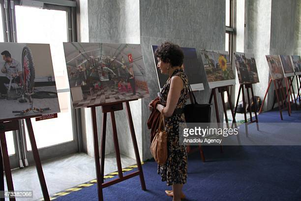 A guest views photographs during an organization held to raise awareness of Syrian conflict including a piano recital performed by teenage pianist...