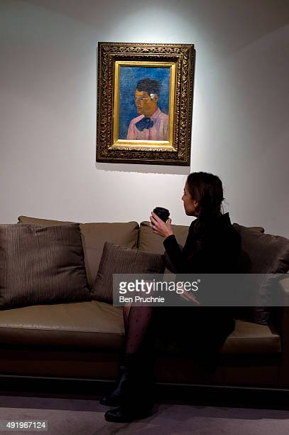 A guest views the painting 'Jeune Homme a la fleur' by Paul Gauguin during the preview ahead of the artist's muse a curated evening sale in...