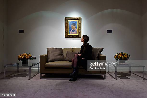 A guest views the painting 'Jeune Homme a la fleur' by Paul Gauguin during the preview ahead of the artist's muse a curated evening sale during...
