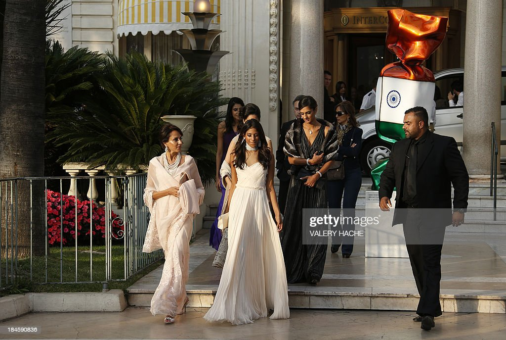 Guest walk in front of the Carlton Hotel in the southeastern French city of Cannes on October 14, 2013 during the wedding of a London-based Indian couple. The Carlton palace was entirely booked for several nights to accomodate guests for the wedding of Kunal Grover and Ria Dubash.