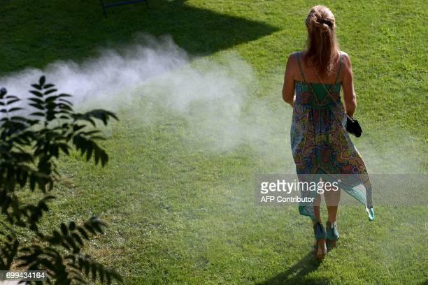 CORRECTION A guest walks through mist during the 65th 'Fete de la Fleur' at Chateau MalarticLagraviere in Leognan southwestern France on June 21...
