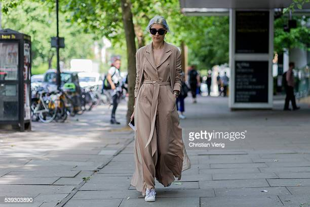 A guest wearing a beige brown dress outside Topman during The London Collections Men SS17 on June 10 2016 in London England