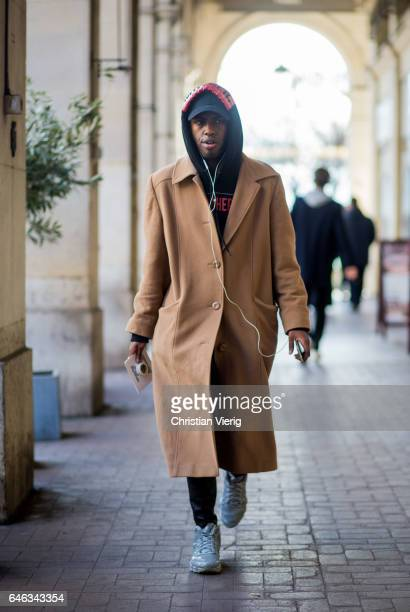 A guest wearing a beige coat navy hoody flex cap outside Anrealage on February 28 2017 in Paris France