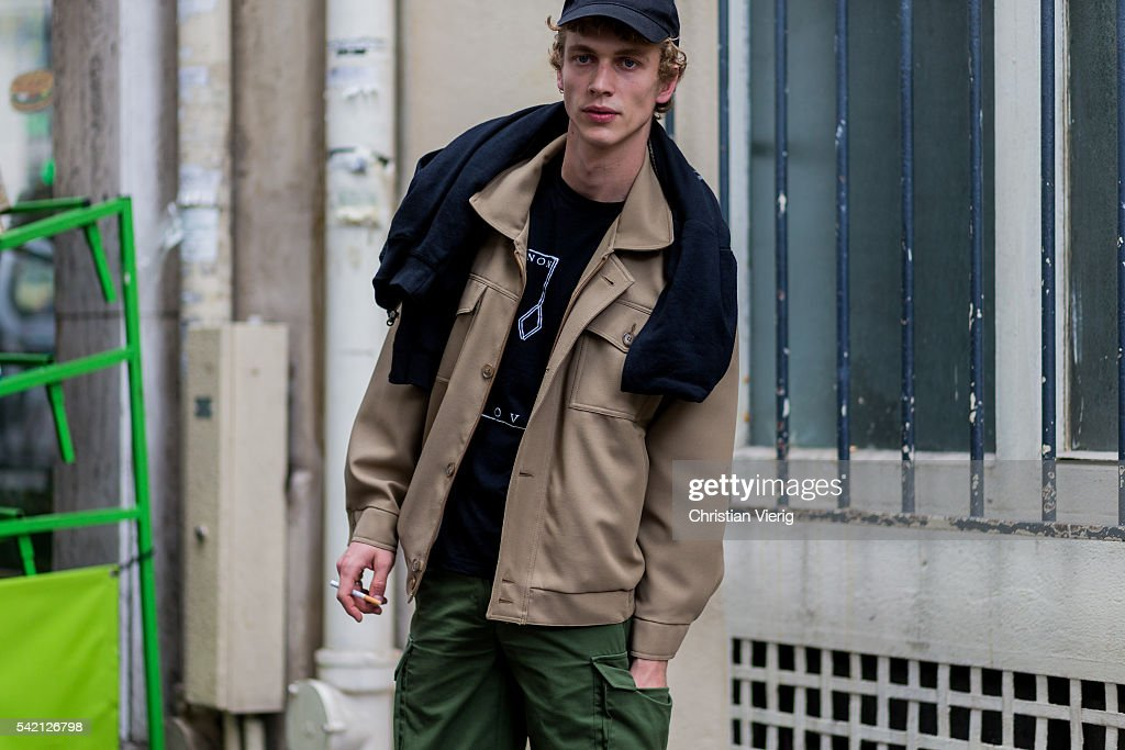 A guest wearing a beige jacket and cap outside Balenciaga during the Paris Fashion Week Menswear Spring/Summer 2017 on June 22 2016 in Paris France